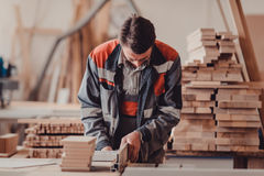 A carpenter works on woodworking the machine tool. Carpenter working on woodworking machines in carpentry shop. stock photo
