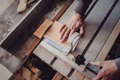 A carpenter works on woodworking the machine tool. Carpenter working on woodworking machines in carpentry shop. Royalty Free Stock Photo