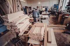 A carpenter works on woodworking the machine tool. Carpenter working on woodworking machines in carpentry shop. Man collects furniture boxes. view from the royalty free stock image