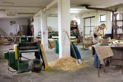 Carpenter workshop. The inside of a carpenter workshop, a man working at one of the tables, some machines Stock Image