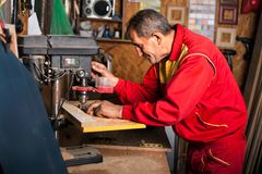 Carpenter using drill press to mae hole in wooden plank. Carpenter in the workshop, drill in hand Stock Images