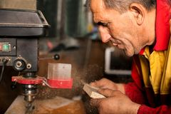 Carpenter using drill press to mae hole in wooden plank. Carpenter in the workshop, drill in hand Royalty Free Stock Photo
