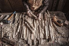 Carpenter in workshop. Hold carved wood stock image