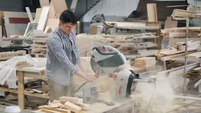 Carpenter cleaning circular saw from sawdust working in workshop indoors. Carpenter young handsome guy in casual clothes is cleaning circular saw from sawdust stock video footage