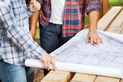 Carpenters Analyzing Blueprint At Site Stock Image