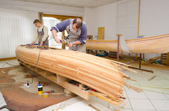Carpenters assembling new canoe of their own design Royalty Free Stock Images