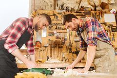 Carpenters with blueprint at workshop Stock Images