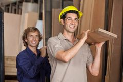 Carpenters Carrying Plank While Looking Away Royalty Free Stock Image