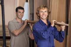 Carpenters Carrying Plank On Shoulders In Workshop Stock Photography