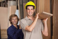 Carpenters Carrying Wooden Plank In Workshop Royalty Free Stock Photos