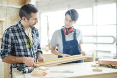 Carpenters checking measurement of wooden plank stock photos