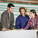 Carpenters Communicating At Table In Workshop Royalty Free Stock Photo