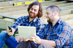 Carpenters comparing notes from phone and tablet. Carpenters checking prices on supplies stock photos