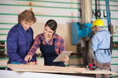 Carpenters With Digital Tablet Communicating In Stock Images
