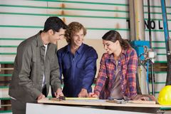 Carpenters Discussing Over Blueprint At Table Royalty Free Stock Photos