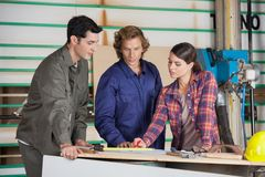 Carpenters Discussing At Table In Workshop Stock Images