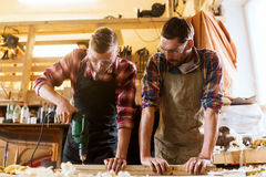 Carpenters with drill drilling plank at workshop. Profession, carpentry, woodwork and people concept - two carpenters with electric drill drilling wood plank at stock photo