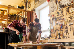 Carpenters with drill drilling plank at workshop Royalty Free Stock Photo