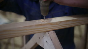 Carpenters drill a hole and fasten a screw with a screwdriver stock footage