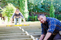 Carpenters with drill and level. Carpenters using drill and level on deck stock photography