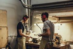Carpenters in earmuffs standing near workbench royalty free stock photo