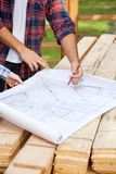 Carpenters Examining Blueprint At Site Stock Image