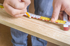 Carpenters hands with pencil and measuring tape Stock Image