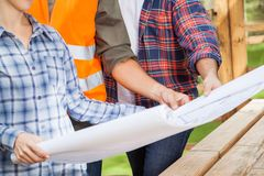 Carpenters Holding Blueprint At Site Stock Image
