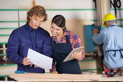 Carpenters Holding Digital Tablet And Documents Stock Photo