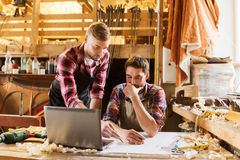 Carpenters with laptop and blueprint at workshop Stock Image