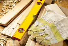 Carpenters level, nails and work gloves. Are on a wooden planks Stock Photos