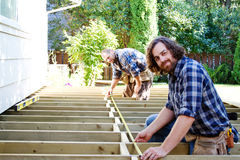 Carpenters measuring. Two carpenters measuring deck with tape stock photography