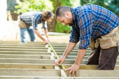 Carpenters Measuring Wood With Tape At Stock Image