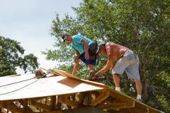 Carpenters Nailing Plywood. Carpenters use a pneumatic nail gun to secure plywood sheathing to the truss rafters of a home royalty free stock image