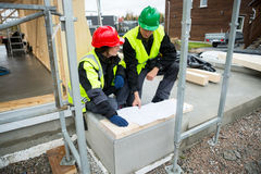 Carpenters With Plan Sitting At Construction Site Stock Photography