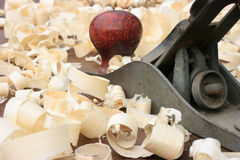 Carpenters Plane and Wood Shavings. Carpenters plane on a workbench surrounded by wood shavings Stock Image