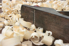 Carpenters Plane and Wood Shavings. Carpenters plane laying on its side surrounded by wood shavings Royalty Free Stock Photos