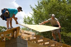Carpenters With Plywood. Two carpenters place plywood onto trusses to be nailed down for the roof stock photography