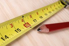 Carpenters rule and pencil. Closeup image of measuring tape and carpenters pencil royalty free stock images