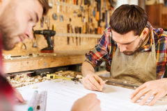Carpenters with ruler and blueprint at workshop Stock Photos