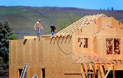 Carpenters Setting Trusses. Two carpenters with a nail gun wearing leather nail bags working setting trusses on a roof of a house that is under construction Stock Images