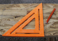 Carpenters speed square. An orange carpenters speed square and an orange carpenters pencil on a LVL beam Royalty Free Stock Photo