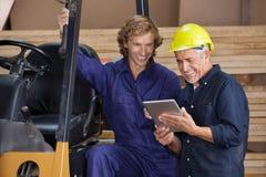 Carpenters Using Digital Tablet In Workshop. Male carpenters using digital tablet together in workshop Royalty Free Stock Photo