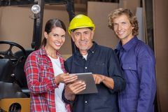 Carpenters Using Digital Tablet In Workshop Royalty Free Stock Images