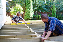 Carpenters using level and checking their work. Carpenters checking their work on deck royalty free stock photos