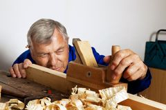 Carpenters with wood. A carpenter with a planer and wood shavings in the workshop royalty free stock photo