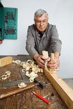 Carpenters with wood. A carpenter with a planer and wood shavings in the workshop stock image