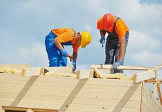 Carpenters at wooden roof work. Two construction carpenters roofers workers installing wood board roof Royalty Free Stock Photo