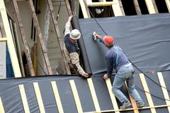 Carpenters at work. Two carpenters working on a roof