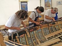 Carpenters are working on the restoration of an old wooden boat. Brest, France - July 14, 2008: Croatian traditional shipbuilders are working on the restoration Royalty Free Stock Photo